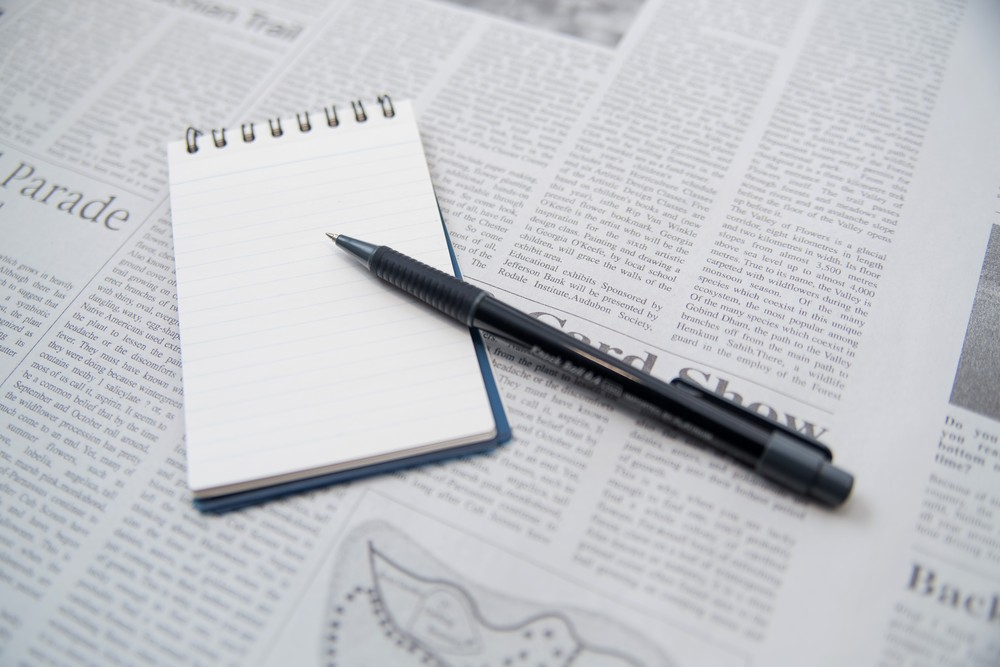 英字新聞とメモとペン